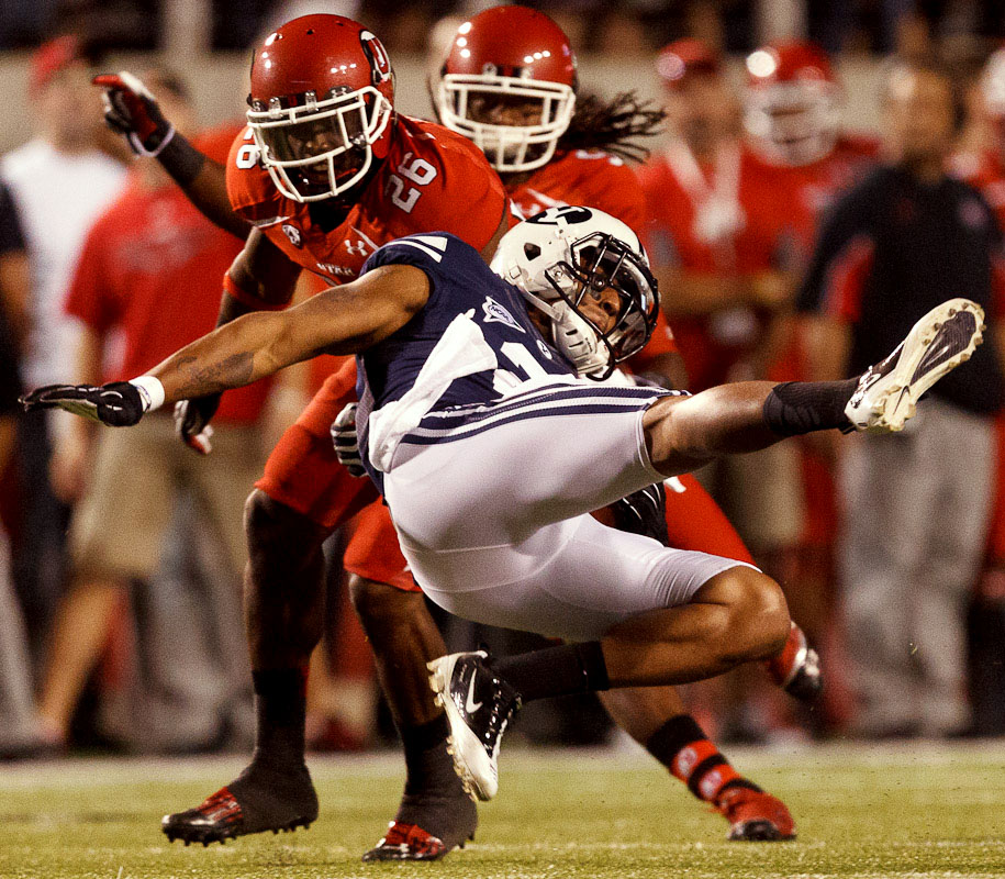 Utah defensive back Ryan Lacy (26) pulls down Brigham Young wide receiver Cody Hoffman (2) as Utah hosts BYU college football in Salt Lake City, Utah, Saturday, September 15, 2012